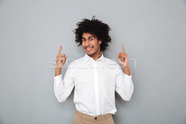 Portrait of a happy cheery african man in white shirt Stock photo © deandrobot