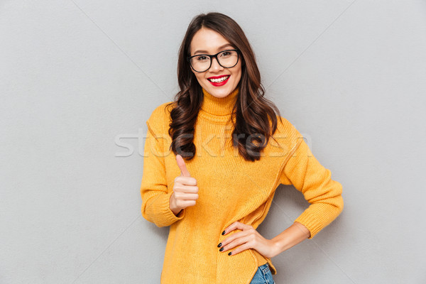 Smiling woman in sweater and eyeglasses with arm on hip Stock photo © deandrobot
