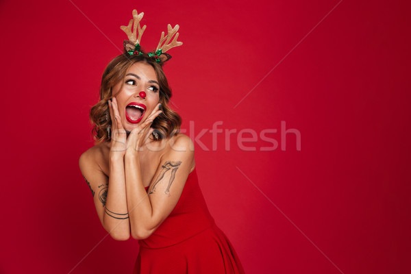 Portrait of an excited happy girl wearing christmas deer costume Stock photo © deandrobot