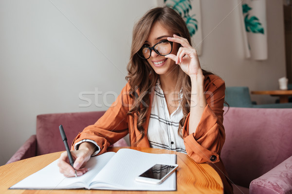 Portrait femme prendre des notes notepad séance table Photo stock © deandrobot