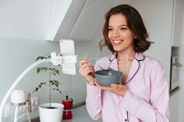 Portrait of a lovely smiling woman in pajamas Stock photo © deandrobot
