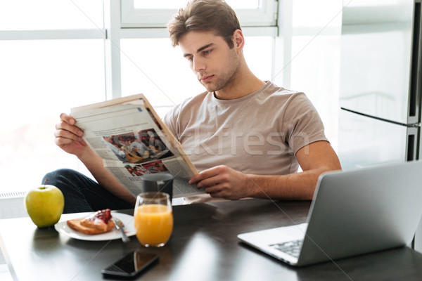 Young concentrated man reading newspaper while sitting in kitchen Stock photo © deandrobot