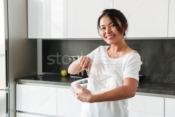 Smiling young woman standing at the kitchen in home Stock photo © deandrobot
