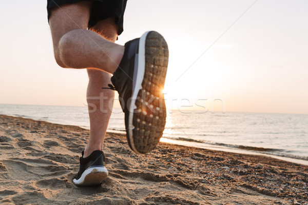 Back view of a sportsmen's legs running on a sand Stock photo © deandrobot