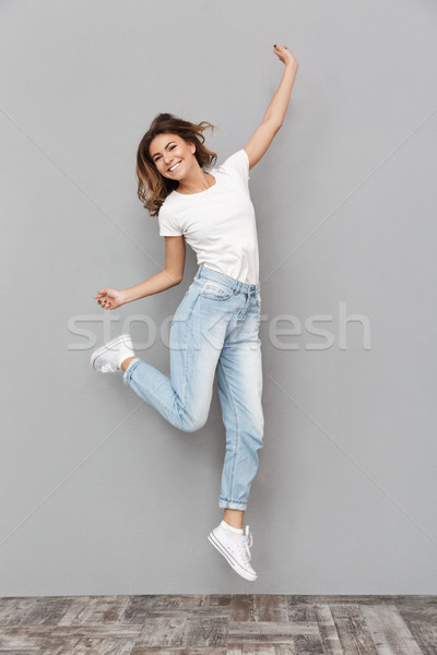 Full length portrait of a cheerful young woman jumping Stock photo © deandrobot