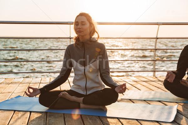 Csinos fiatal lány meditál ül fitnessz víz Stock fotó © deandrobot