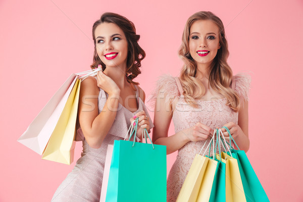 Two Smiling women in dresses holding packages while posing together Stock photo © deandrobot