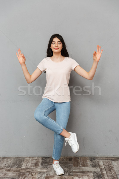 Beautiful young lady isolated over grey background Stock photo © deandrobot