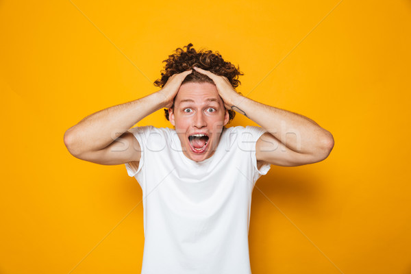Portrait of emotional shocked guy with curly brown hair screamin Stock photo © deandrobot