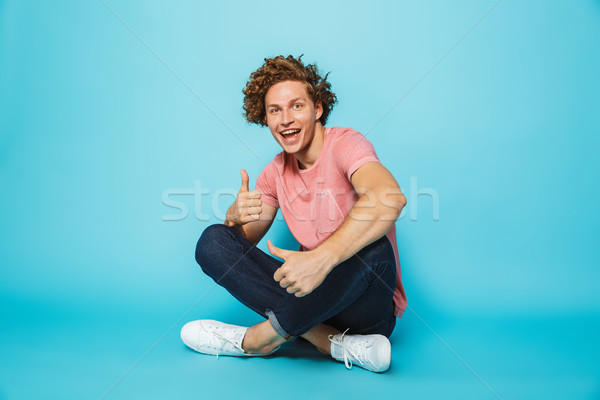 Portrait of a cheerful young curly haired man showing Stock photo © deandrobot
