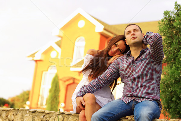 Happy couple sitting in the garden in front of new home Stock photo © deandrobot