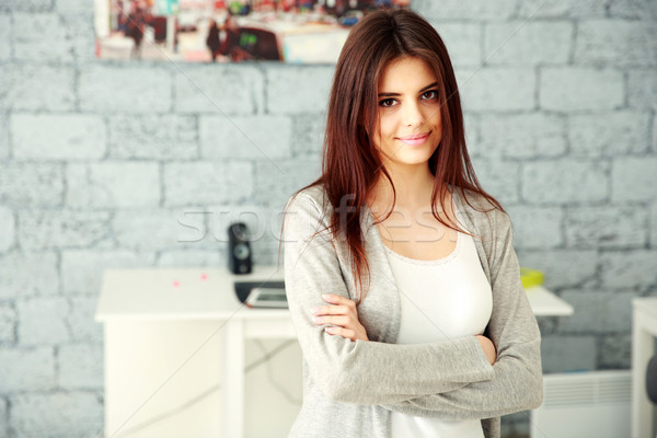 Young smiling businesswoman with arms folded standing at office Stock photo © deandrobot