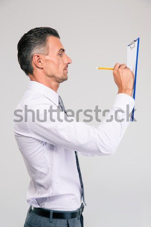 Thoughtful male doctor with clipboard and stethoscope standing over a white background Stock photo © deandrobot