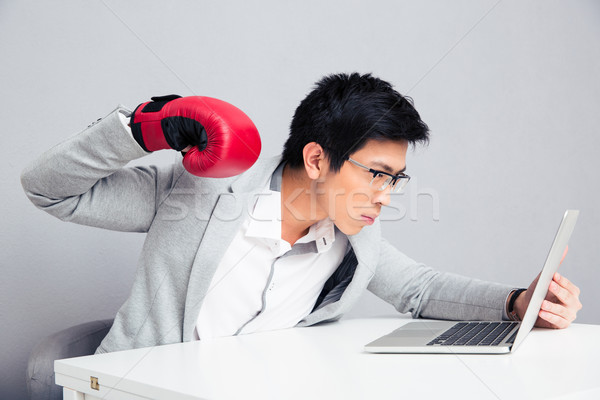 Businessman in boxing gloves reading to hit laptop  Stock photo © deandrobot