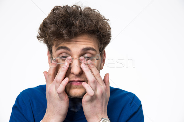 Stock photo: Young businessman rubbing his eyes over white background