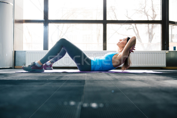 Young woman lying on the yoga mat and doing fitness exercise Stock photo © deandrobot