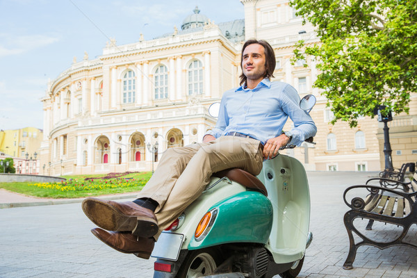 Handsome young man resting on scooter Stock photo © deandrobot