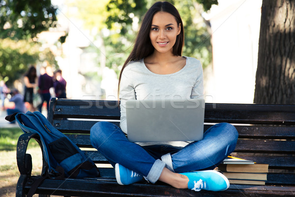 Female student sitting on the bench with laptop  Stock photo © deandrobot