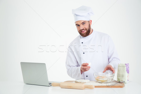 Happy male chef cook baking with laptop  Stock photo © deandrobot