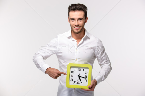 Businessman pointing finger on wall clock  Stock photo © deandrobot