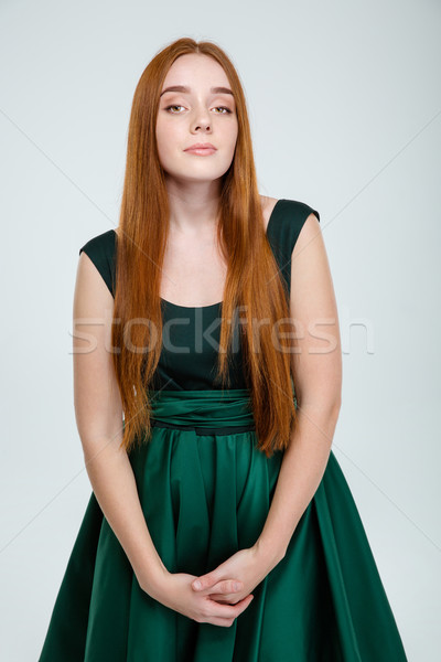 Serious woman in green dress looking at camera Stock photo © deandrobot
