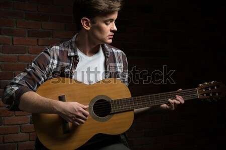Attractive young guitarist playing acoustic guitar Stock photo © deandrobot