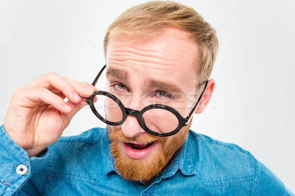 Amusing happy man with beard looking over his round glasses Stock photo © deandrobot