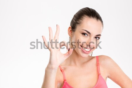 Smiling sporty woman showing ok sign Stock photo © deandrobot