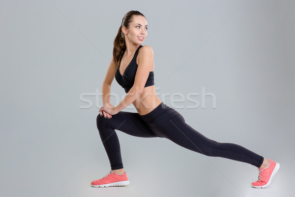 Stock photo: Smiling pretty young sportswoman stretching her legs and looking back