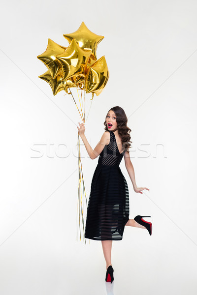 Attractive playful happy woman looking back and holding golden balloons Stock photo © deandrobot