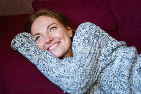 Portrait of cheerful woman in knitted sweater lying on couch Stock photo © deandrobot