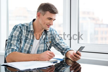 Attractive male sitting and working in the office Stock photo © deandrobot