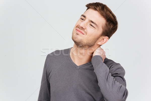 Sad unhappy man in grey pullover suffering from neck pain Stock photo © deandrobot