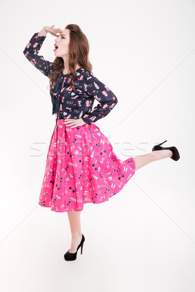 Pretty amusing young woman standing and looking far away Stock photo © deandrobot