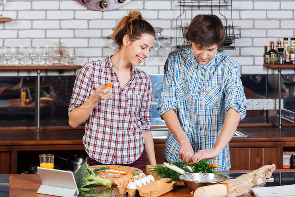 Stock photo: Beautiful couple standing and cooking together on kitchen