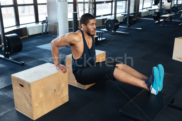 Strong fitness man pumps biceps using training apparatus Stock photo © deandrobot