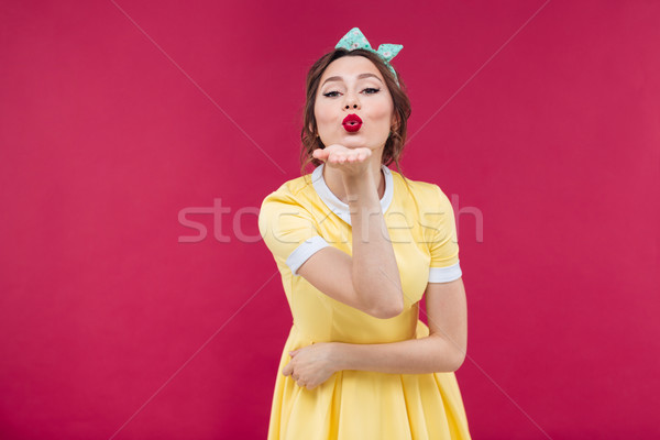 Cute charming young woman standing and sending a kiss Stock photo © deandrobot