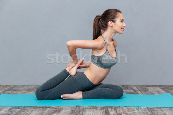 Young woman doing yoga exercise one legged king pigeon Stock photo © deandrobot