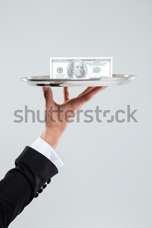 Hand of waiter in white glove holding tray with dollars Stock photo © deandrobot