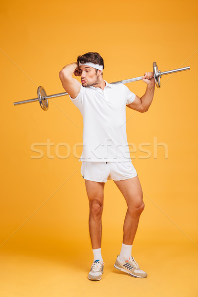 Amusing young sortsman with barbell showing and kissing his biceps Stock photo © deandrobot