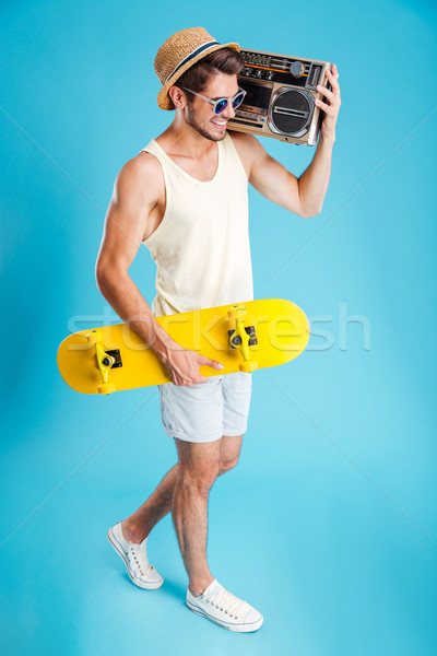 Happy young man with boombox walking and holding skateboard Stock photo © deandrobot