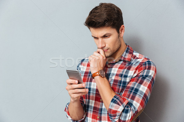 Сток-фото: задумчивый · молодым · человеком · рубашку · мобильного · телефона · серый