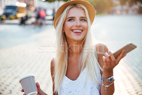 Portrait of a girl in hat holding cup and smartphone Stock photo © deandrobot
