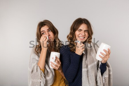 Two happy joking and sad frowning young women drinking tea Stock photo © deandrobot