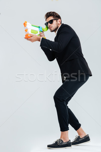 Full length portrait of focused businessman shooting with water gun Stock photo © deandrobot