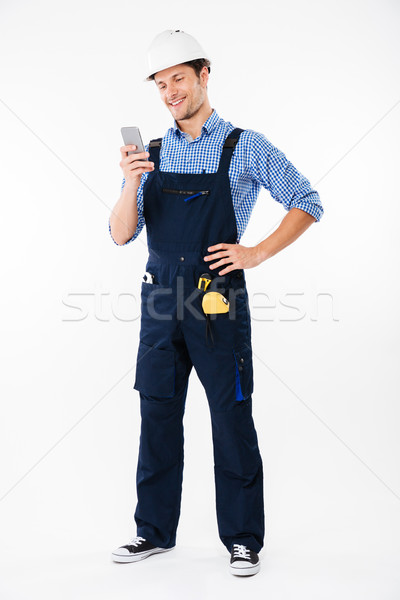 Full length portrait of a builder standing and using phone Stock photo © deandrobot