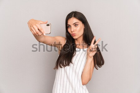 Happy woman sending air kiss and taking selfie with smatphone Stock photo © deandrobot