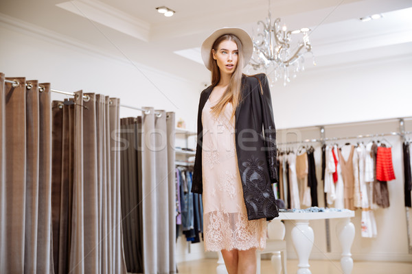 Attractive young woman in hat standing in clothing shop Stock photo © deandrobot