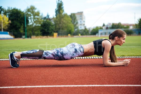 Woman athlete doing plank exercise on stadium Stock photo © deandrobot