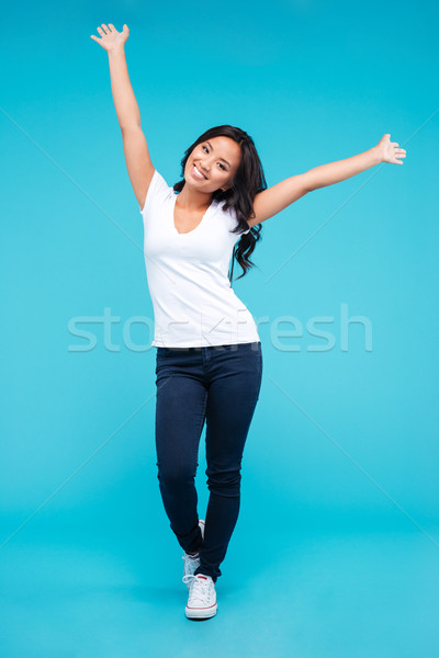 Cheerful young asian woman standing with raised up hands Stock photo © deandrobot